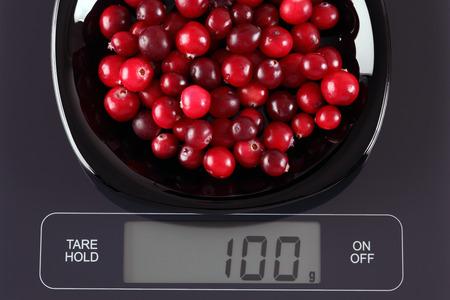 black gram: Cranberries in a black plate on digital scale displaying 100 gram.