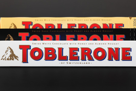 Tambov, Russian Federation - September 23, 2012 100g Toblerone chocolate bars. Swiss white, dark and milk chocolates with honey and almond nougat. Toblerone is made by Kraft Foods. Editorial