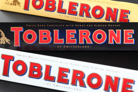 toblerone: Tambov, Russian Federation - September 23, 2012 100g Toblerone chocolate bars. Swiss white, dark and milk chocolates with honey and almond nougat. Toblerone is made by Kraft Foods. Editorial