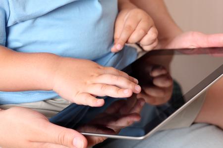 niño empujando: Niño y madre con una tableta digital. Acercamiento. Foto de archivo