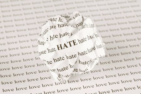 hate: Crumpled paper ball with words Hate