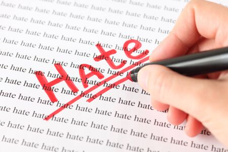 red pen: Womans hand with red pen writing word Hate.