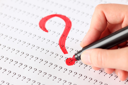 Womans hand with red pen writing Question mark on the background of question marks.