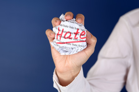 hate: Crumpled paper ball with words Hate in women hand.