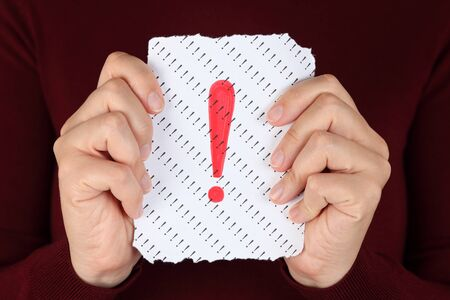 Piece of paper with red Exclamation mark in the womans hands. Stock Photo