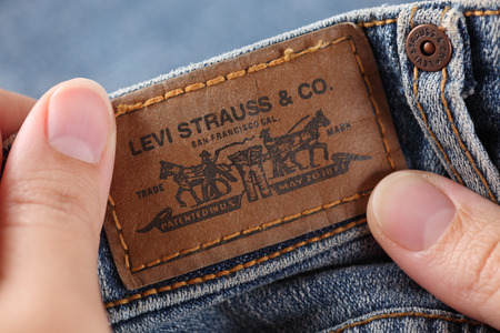 levi: Tambov, Russian Federation - October 21, 2012 Womans hands holding label logo of a pair Levis Jeans. Studio shot. Levi Strauss & Co. is a American clothing company was founded in 1853. It known worldwide for its Levis brand of denim jeans.
