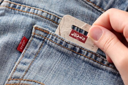 levi: Tambov, Russian Federation - October 21, 2012 Womans hand taking out label logo  from pocket of a pair Levis Jeans. Studio shot. Levi Strauss & Co. is a American clothing company was founded in 1853. It known worldwide for its Levis brand of denim jean Editorial