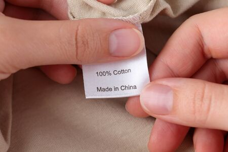 made in china: Womans hands holding clothes label. 100% cotton. Made in China. Stock Photo