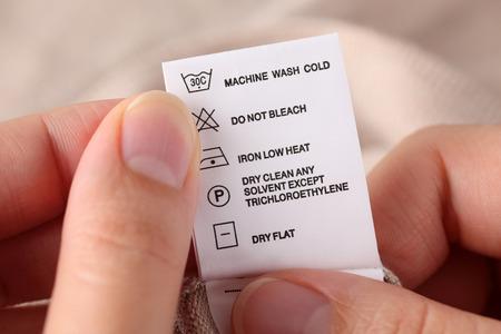 Manos de la mujer que sostienen la ropa etiqueta con instrucciones de limpieza.