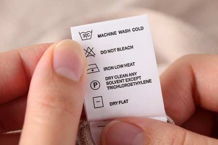 Womans hands holding clothes label with cleaning instructions. Stock Photo