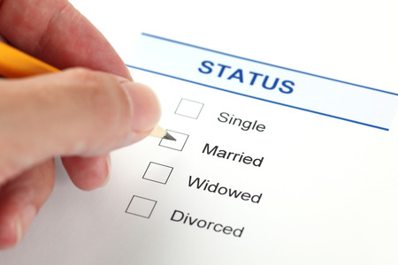 marital: Marital status form with checkbox and human hand with pencil. Stock Photo