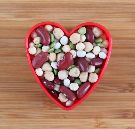 legume: Mixed legume beans in a heart bowl. Close-up.