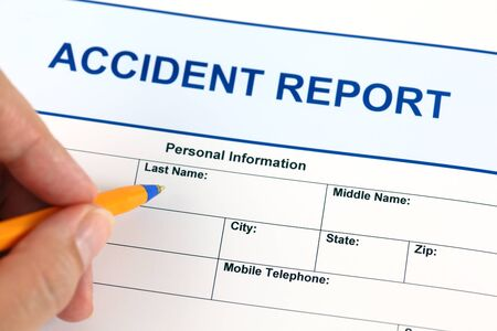 Accident report application form and human hand with ballpoint pen.