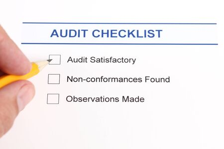 satisfactory: Audit checklist and human hand with pencil. Stock Photo