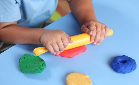 Les mains des enfants avec rouleau à pâtisserie jouer la pâte à modeler.