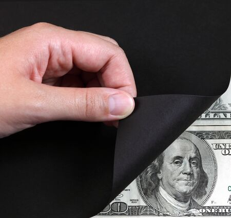 turning page: Womans hand turning a black page and 100 dollar banknote.