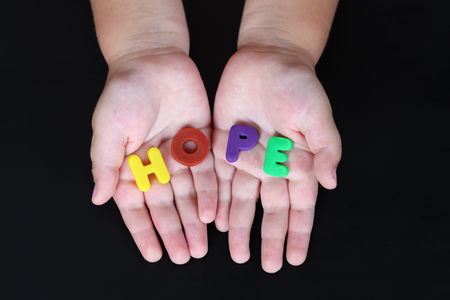 child's play clay: Word Hope in childs hands on black . Letters is made of childs play clay.