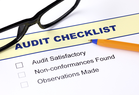 Audit checklist with ballpoint pen and glasses