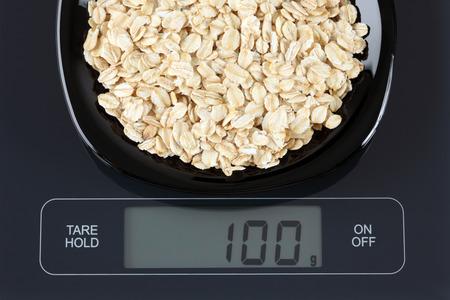 black gram: Oatmeal in a black plate on digital scale displaying 100 gram.