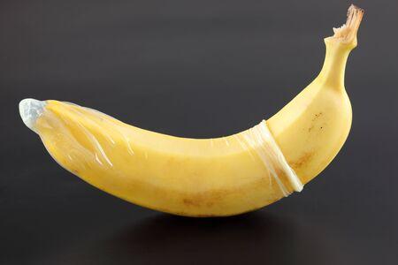 Plátano con condón sobre fondo negro
