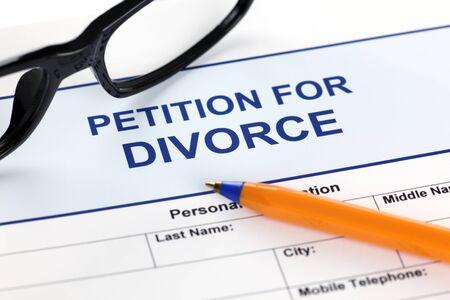 Petitie voor echtscheiding met een bril en balpen.
