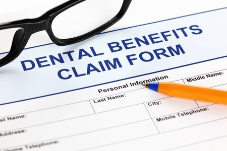 dental: Dental benefits claim form with glasses and ballpoint pen.