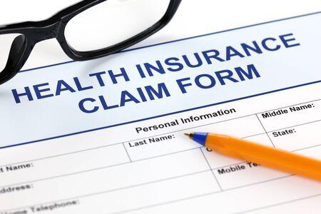 reimbursement: Health insurance claim form with glasses and ballpoint pen. Stock Photo