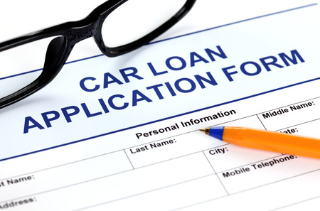 Car loan application form with glasses and ballpoint pen.