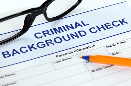 Criminal check application form with glasses and ballpoint pen.