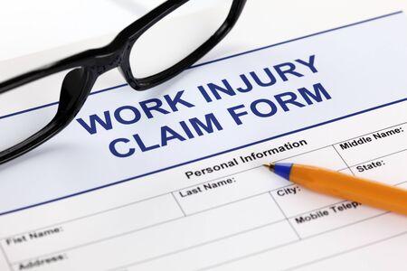 Work Injury claim form glasses and ballpoint pen Standard-Bild