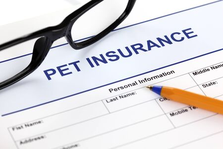 Pet insurance form with glasses and ballpoint pen.
