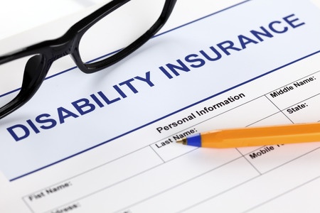 Disability insurance form with glasses and ballpoint pen.