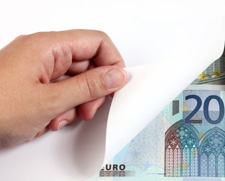 turning page: Womans hand turning a white page and 20 euro banknote. Stock Photo
