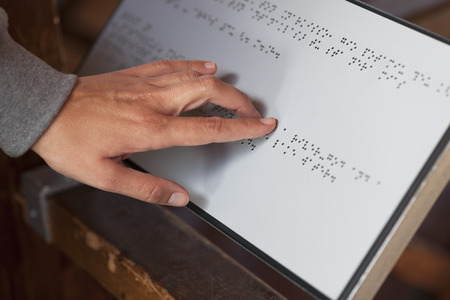 braille: Closeup of human hand reading braille sign.