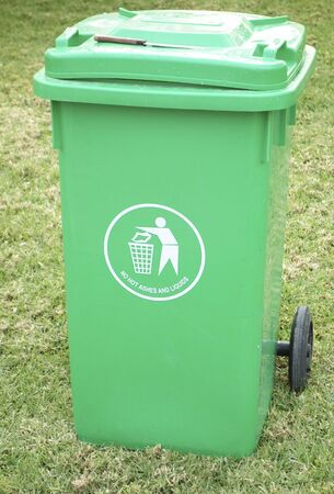 wastepaper basket: Outdoor green garbage can with knife on it top