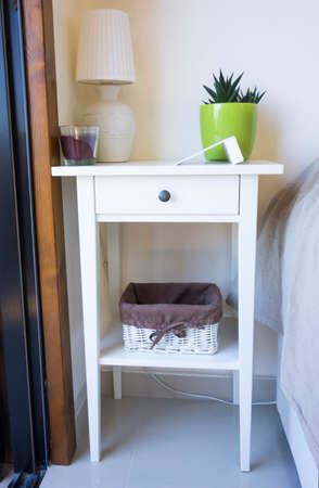 'bedside table': White bedside table with table lamp, candle, flower pot, basket and clock in bedroom.