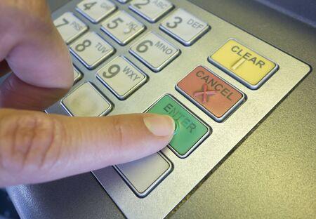 pressing: Womans hand pressing Enter key on ATM