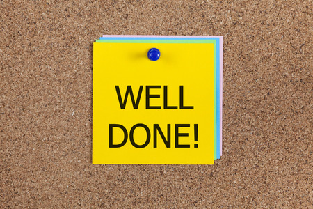 job posting: Post-it notes with word Well done! on corkboard (bulletin board). Stock Photo