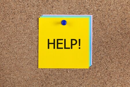 straight pin: paper notes with word Help! on corkboard (bulletin board). Stock Photo