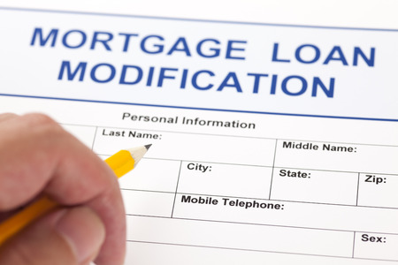 Mortgage Loan Modification application form and human hand with pencil. Standard-Bild