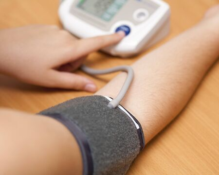 hypertensive: Woman checking blood pressure and heart rate with a digital blood pressure monitor. Stock Photo
