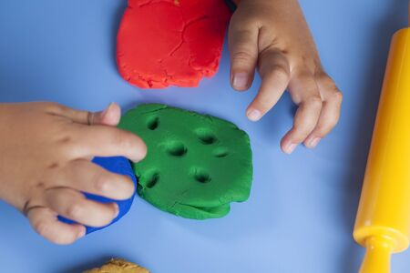 child's play clay: Childrens hands playing with play-clay. Stock Photo