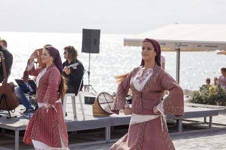 sund: Paphos, Cyprus - November 24, 2013 Two young women in traditional Cypriot costumes dancing to live music on the seafront in Paphos. Paphos Municipal Saths Beach. Traditional Cypriot songs and dancуs with the Anatoli music ensemble. It is a Musical Sund Editorial
