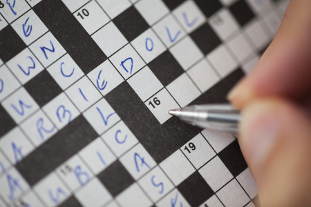 Womans hand with ballpoint pen is filling crossword puzzle. Focus on the crossword field. Stock Photo