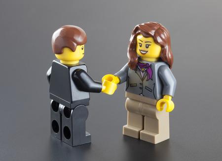 Tambov, Rusland - 4 oktober 2013 Lego figuurtjes zakenman en zakenvrouw schudden handen op een zwarte achtergrond. Studio-opname. LEGO is een populaire lijn van constructiespeelgoed vervaardigd door de Lego Group (Billund, Denemarken). Redactioneel