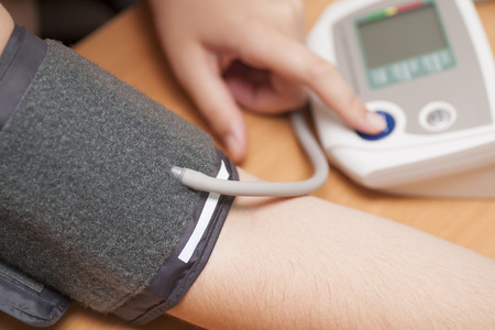 blood pressure monitor: Woman checking blood pressure and heart rate with a digital blood pressure monitor. Stock Photo