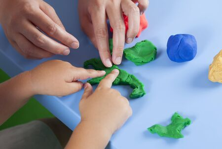 childs play clay: Childrens and mothers hands playing w