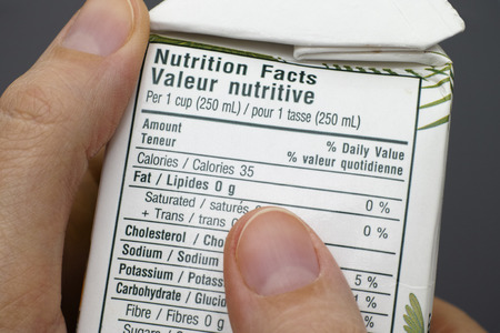 Reading a nutrition facts on tetra pak box with coconut water.