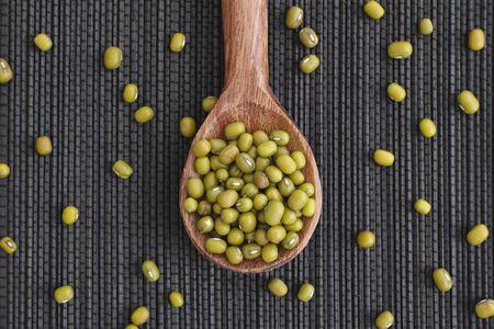 mash: Mung beans (mash) in wooden spoon on black napkin. Stock Photo