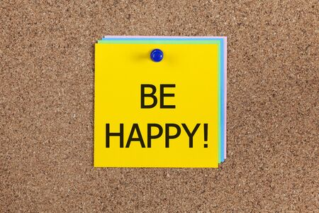 bulletin: paper notes with word Be happy! on corkboard (bulletin board).